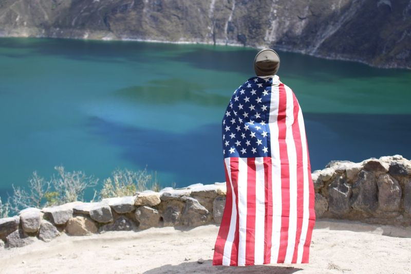 Rear view of man with american flag standing by lake