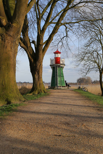 A person relaxing at an old lighthouse - distant view #breakfast #relax Animal Themes Architecture Bare Tree Beauty In Nature Branch Building Exterior Built Structure Day Lighthouse Mammal Nature Outdoors Real People Scenics Sky Tree