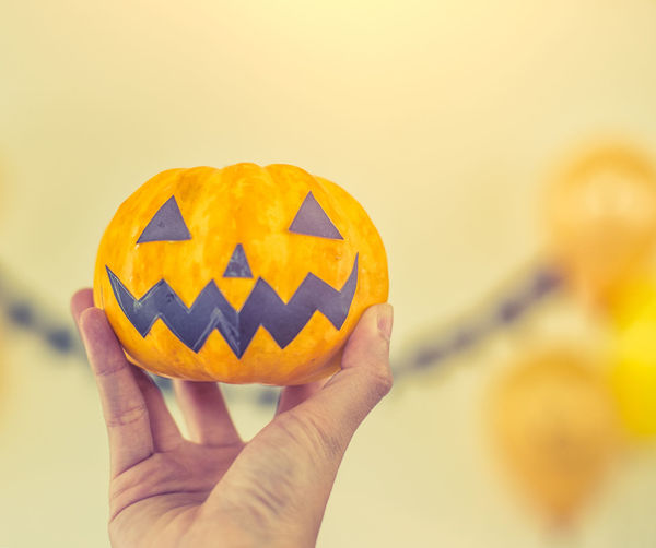 Close-up of person hand holding pumpkin against orange background