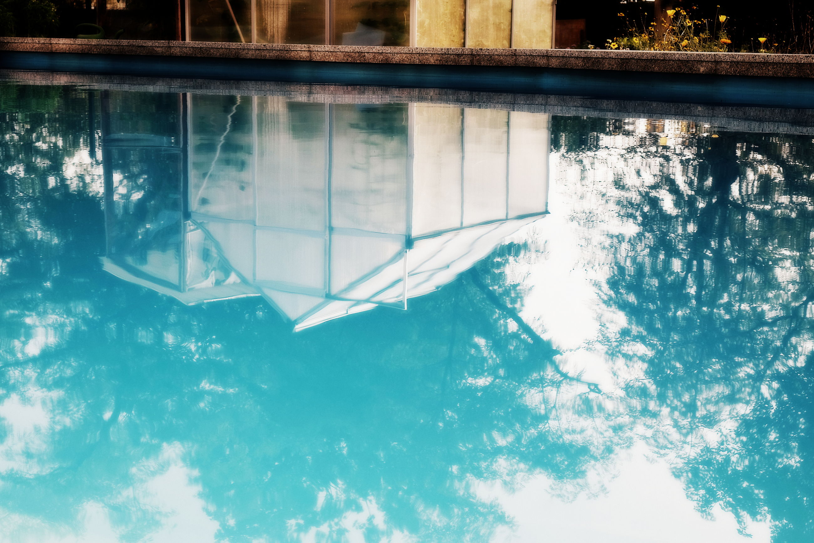 water, pool, reflection, swimming pool, day, nature, waterfront, no people, architecture, built structure, outdoors, sunlight, window, glass - material, transparent, building exterior, blue, sea, high angle view, floating on water