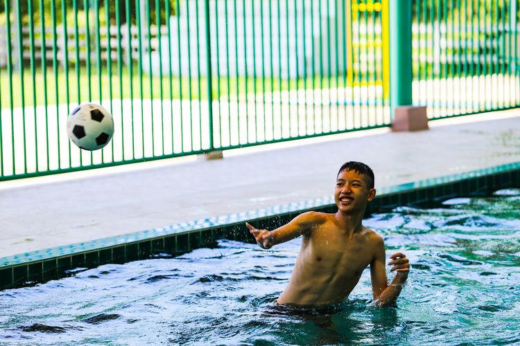 Full length of shirtless man playing in swimming pool