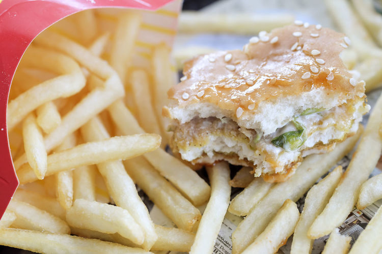 Close-up of half-eaten burger and fries on plate