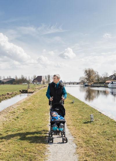 Grandfather Pushing Granddaughter Stroller At Lakeshore