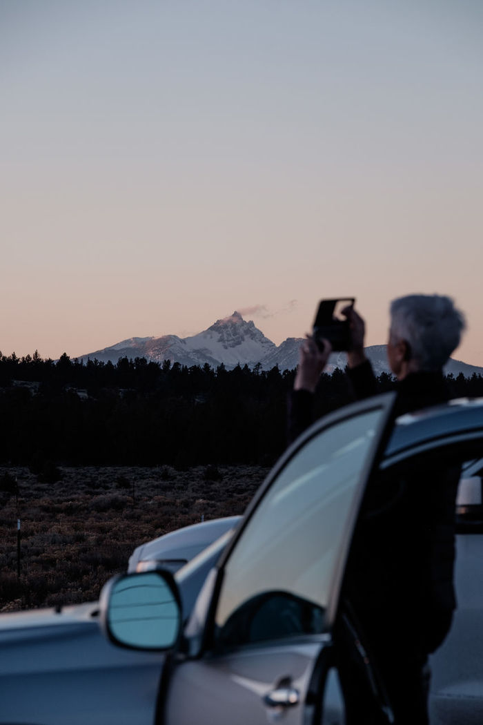 Woman photographing while standing by car against sky during sunset