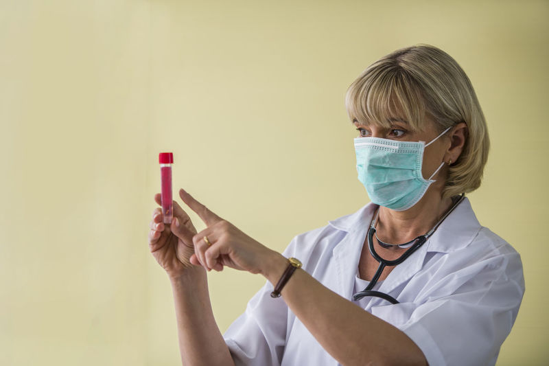 Doctor wearing mask holding test tube against yellow background