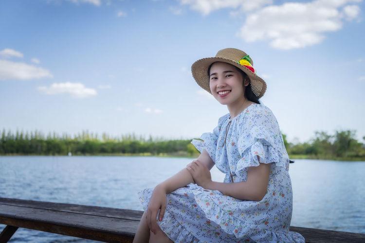 Full length of smiling woman in lake against sky