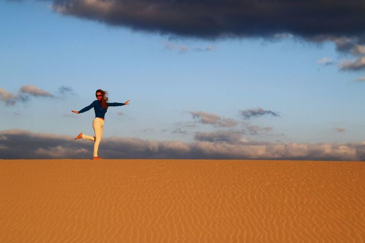 Woman Standing On One Leg With Arms Outstretched In Desert Against Sky