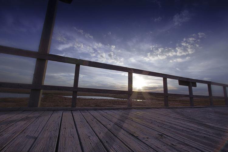 Boardwalk On Field Against Sky