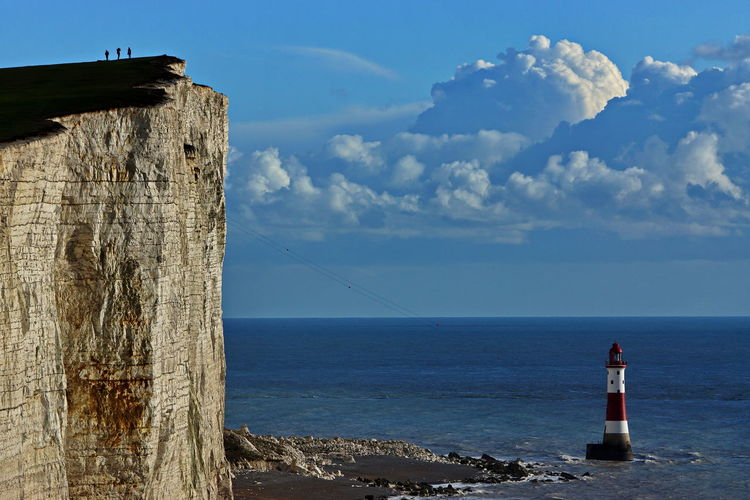 Beachy head lighthouse in sea at seven sisters against sky