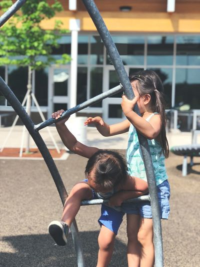 Siblings Climbing On Play Equipment At Playground