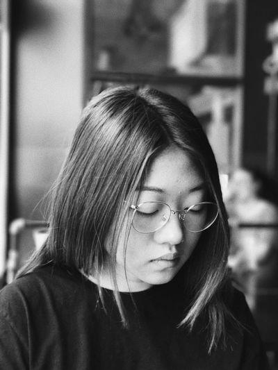 Close-up of woman wearing eyeglasses while sitting at handlebar restaurant