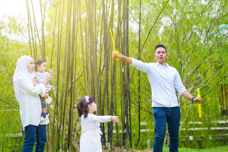 Playful family spending time together at park. Group Of People Men Standing Togetherness Offspring Happiness Plant Childhood Males  Casual Clothing Boys Three Quarter Length Women Emotion Tree Smiling Family Nature Child Limb Human Limb Positive Emotion Body Part Human Arm Son