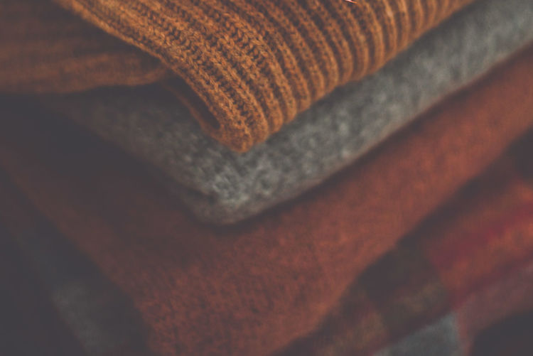 Full frame shot of sweaters stacked at home