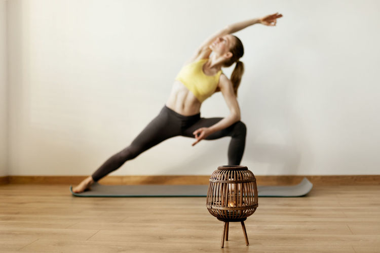 Close-up of oil lamp on floor with woman exercising in background against wall