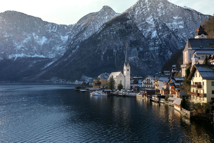 Panoramic view of lake and buildings in hallstatt against mountain during winter