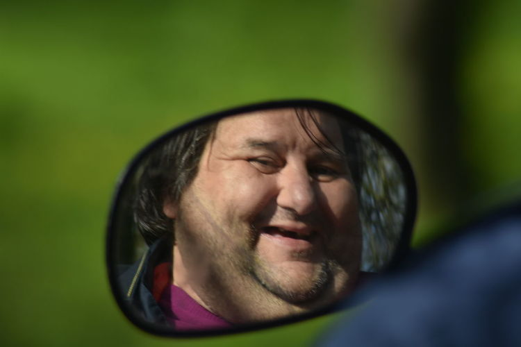Reflection of happy man on rear-view mirror of car
