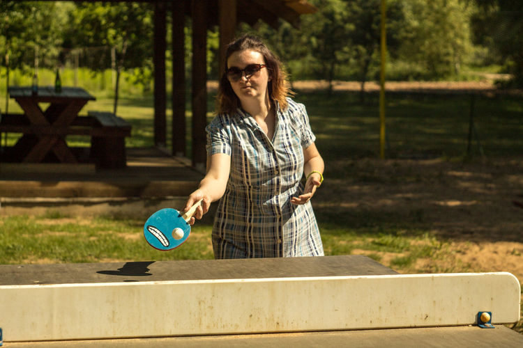 Mid adult woman playing table tennis at park