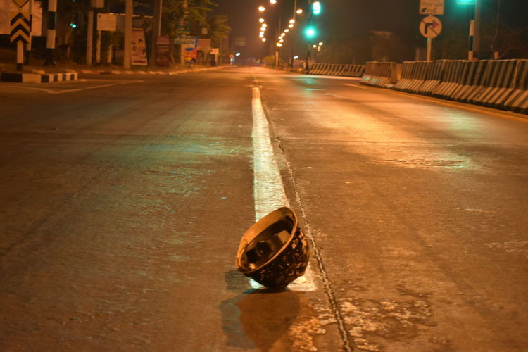 dangerous ride without helmet Clear Street No Helmet Dangerous Ride Empty Street Helmet Fallen In Middle Of Street At Night No Night Traffic Prevent Serious Injuries Protect Skull