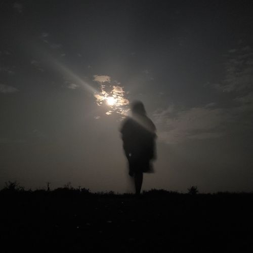 Rear view of silhouette person standing on field against sky