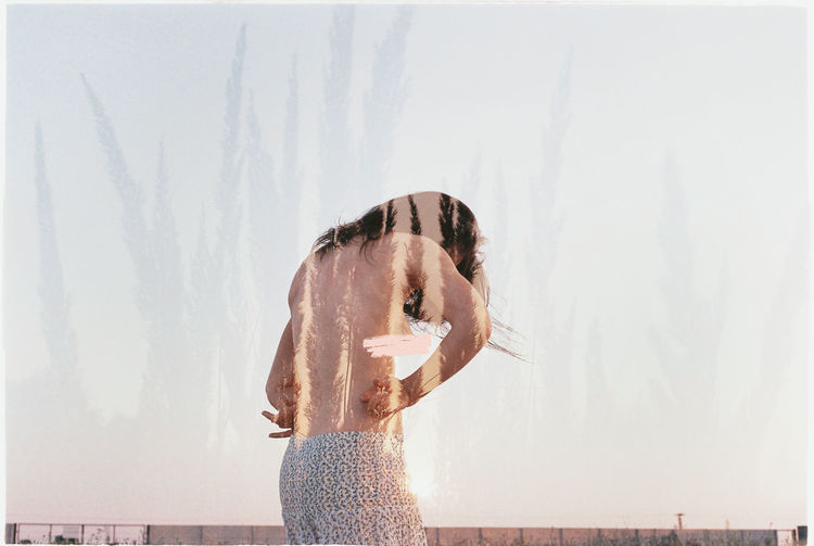 Double Exposure Of Topless Young Woman And Plants Against Sky