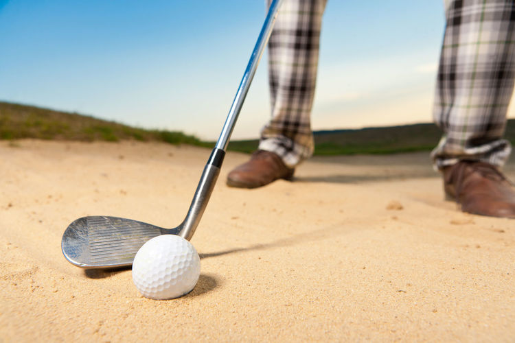 Low Section Of Person Playing Golf On Sand