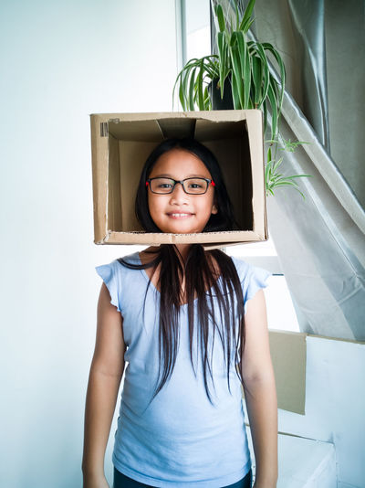Portrait of smiling girl wearing cardboard box