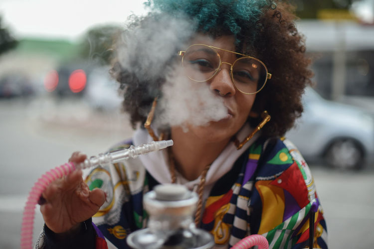 Portrait Of Young Woman Smoking Hookah Holding Sunglasses