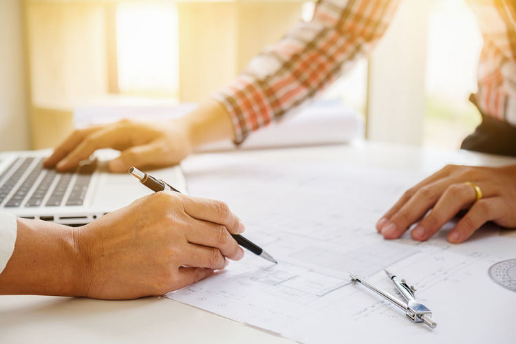 Architects preparing blueprint on desk at office