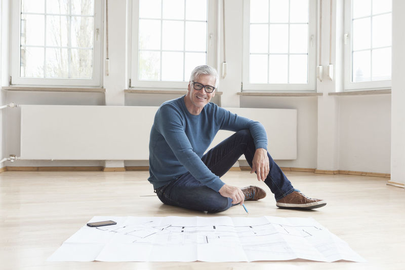 Portrait of man sitting on floor against wall