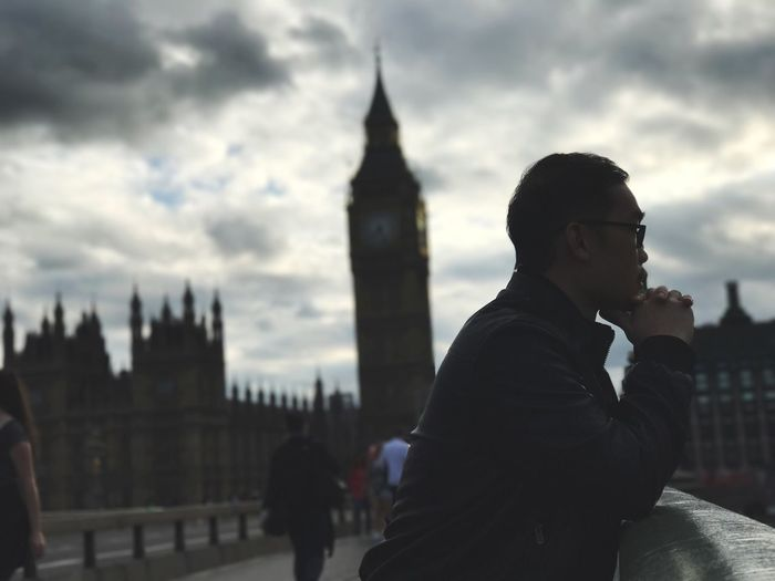 Side view of young man standing on westminster bridge