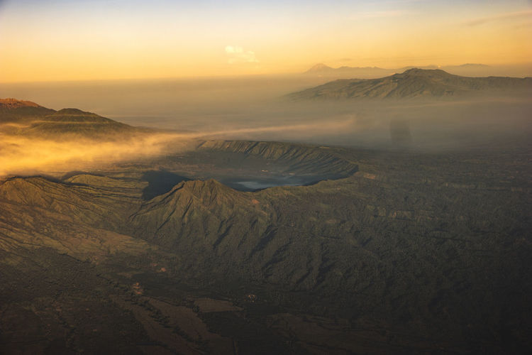 Aerial view of volcanic landscape against sky during sunset