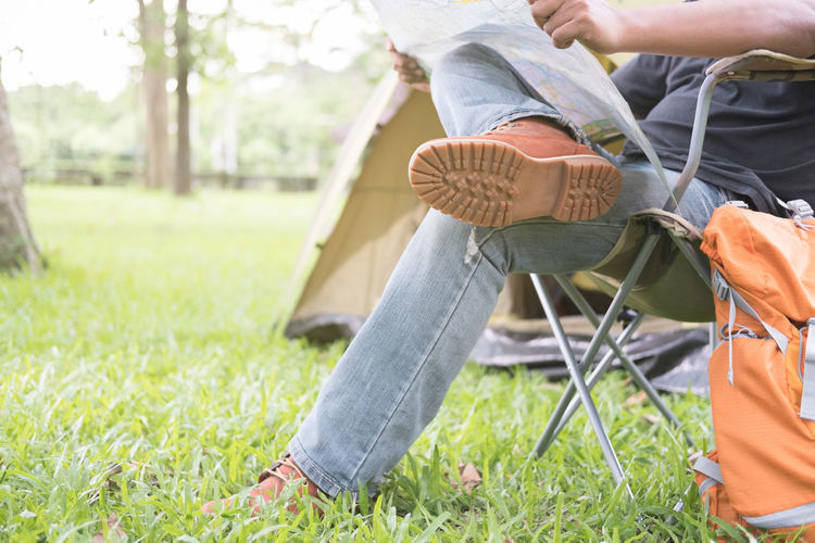 Low section of man sitting on chair at campsite