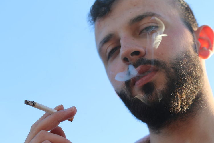 Close-up portrait of young man smoking against sky