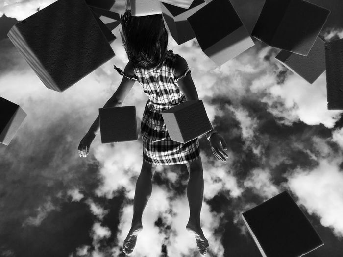 Low Angle View Of Woman Levitating Amidst Blocks Against Sky