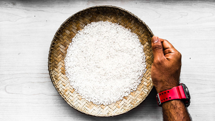 Cropped hand holding rice in wicker container on table