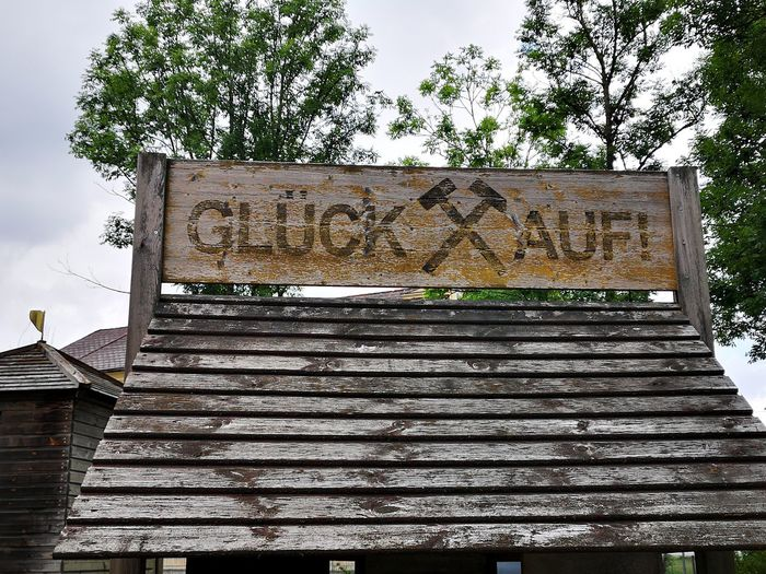 Low angle view of text on old building against sky