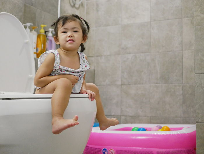A 25 months old Asian baby girl sitting on an adult-size toilet for a toilet training Childhood Child Bathroom One Person Sitting Lifestyles Home Cute Hygiene Potty Training Toilet Training Baby Kid Toddler  Girl Learning Practice At Home Sanitory Habit Routine Happy Enjoy Fun Adult-size Pooping Peeing Urinating Poo Poop Pee Take A Leak Asian  Indoors  Domestic Bathroom Innocence Females Cute Adorable Lovely
