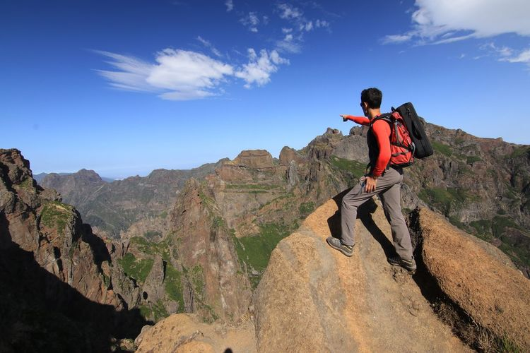 Man Standing On Rock At Mountain Against Sky