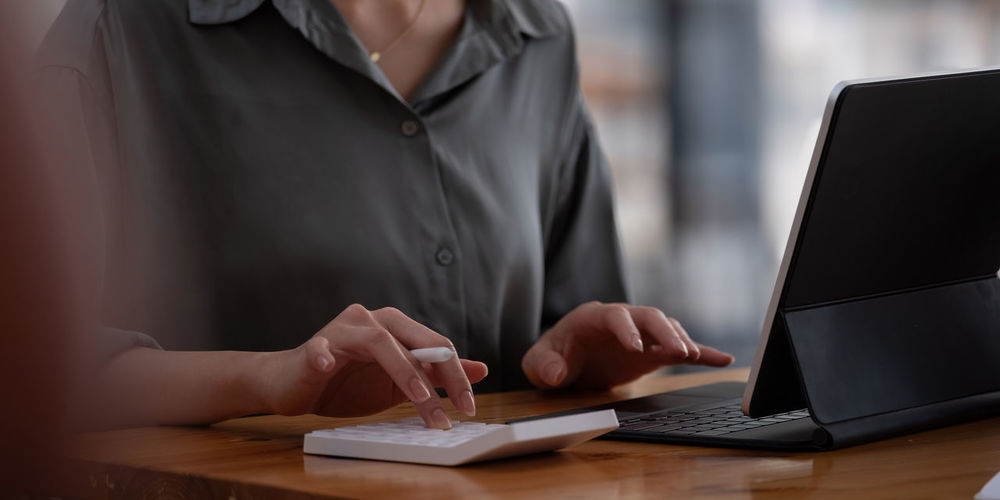 Close up view of bookkeeper or financial inspector hands making report, calculating