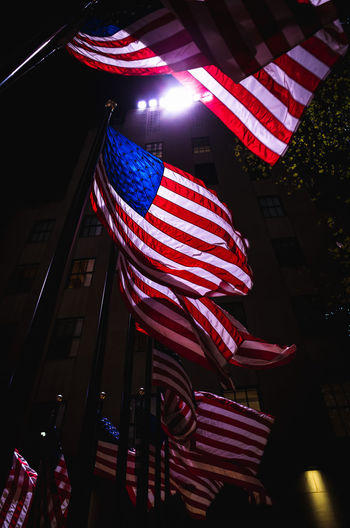 Low angle view of flags on illuminated city at night