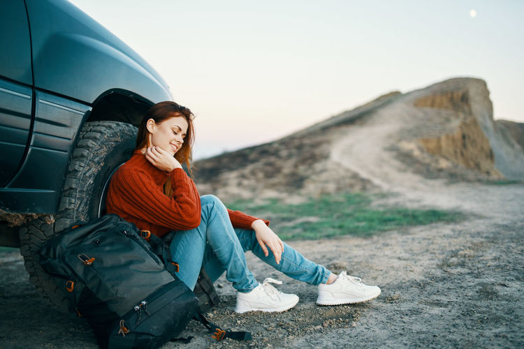 Full length of woman sitting by car against sky