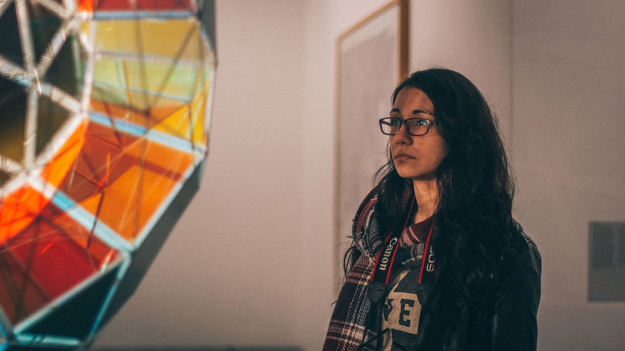 Thoughtful woman in eyeglasses looking away at museum