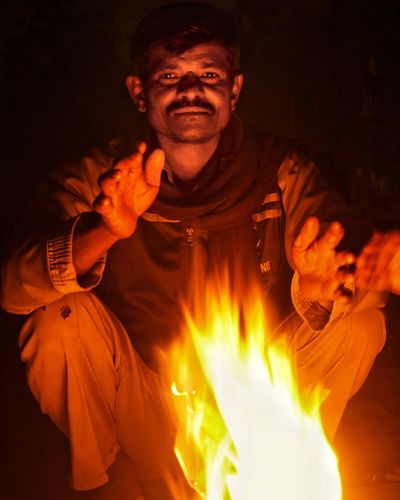 Portrait of man crouching by fire at night