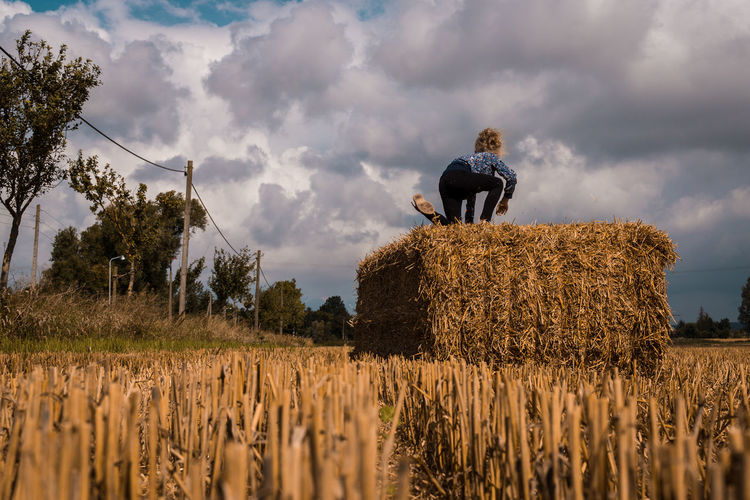 Girl Climbing On Hay Bale Against Sky