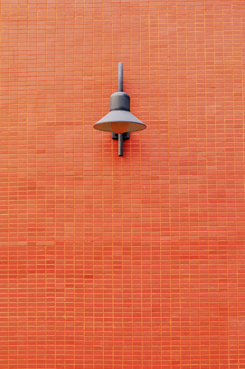 Low angle view of lamp on brick wall