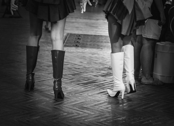 Low section of women in latex boots walking at footpath