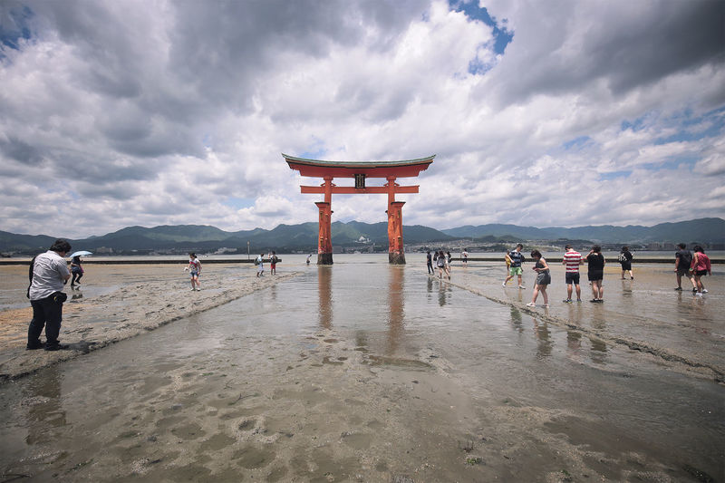 People By Torii Gate In River Against Cloudy Sky