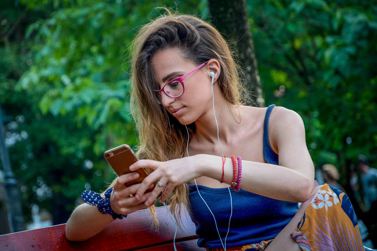 Young woman using mobile phone while sitting in public park
