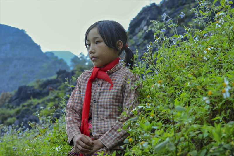 Unidentified young Vietnamese pose for camera with beautiful natural landscape along the Dong Van National Geopark in Ha Giang, Vietnam. Plant Casual Clothing Nature Outdoors One Person Real People Leisure Activity Child Lifestyles Childhood Day Standing Looking Mountain Land Cute Waist Up Beauty In Nature Innocence Hairstyle