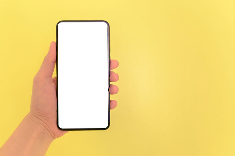 Close-up of hand holding smart phone against yellow background